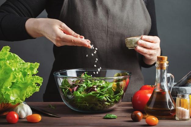 Vrouwenchef-kok in de keuken die salade voorbereiden.
