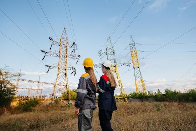 Vrouwencollectief van energiewerkers inspecteert apparatuur en hoogspanningsleidingen. energie.