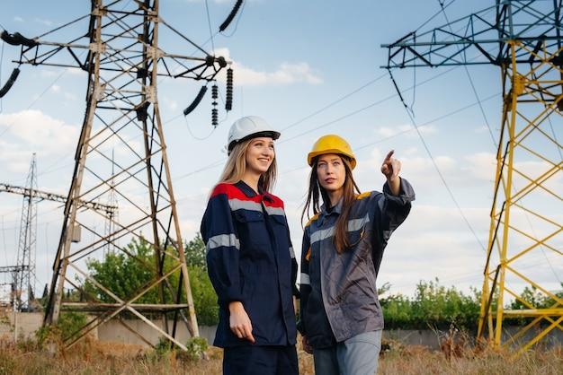 Vrouwencollectief van energiewerkers voert een inspectie uit van apparatuur en hoogspanningsleidingen. energie.