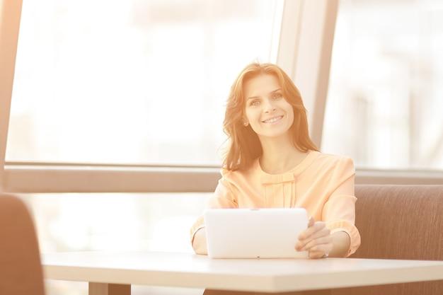 Vrouwenconsulent die een digitale tablet gebruikt op de werkplek op kantoor