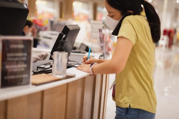 Vrouwenconsument in beschermend maskerhandtekening op transactieontvangstrekening in winkel.