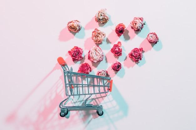Vrouwendag bloemen bezorgen. lege winkelwagen met vallende rozen. ivoor achtergrond met rode schaduwen.