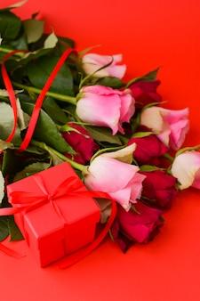 Vrouwendag concept en valentijnsdag wenskaart. samenstelling met cadeau, rozen en envelop. ruimte voor tekst.