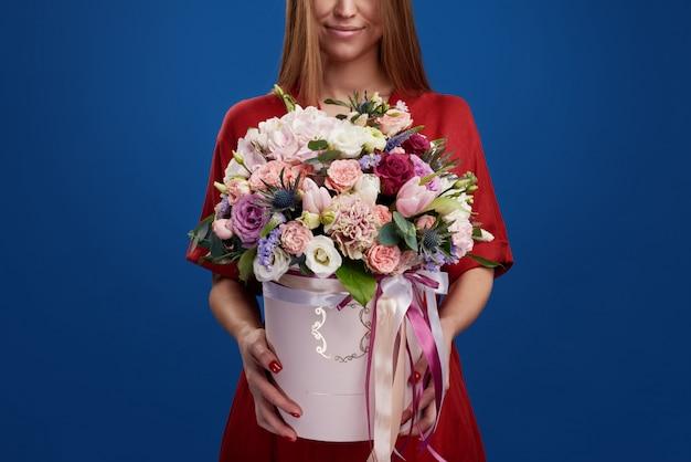 Vrouwendag concept. mode sensuele vrouw in jurk met mooie bloemen boeket in hoedendoos. blauwe ruimte