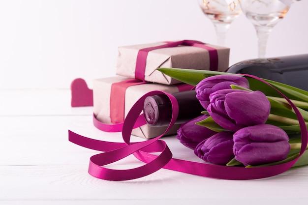 Vrouwendag. geschenken met bloemen en wijn op witte muur