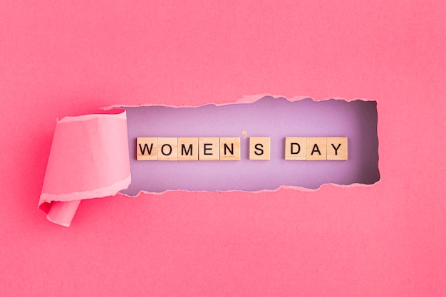 Vrouwendag geschreven in scrabble letters en gescheurd papier
