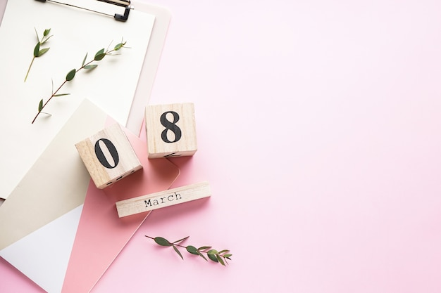Vrouwendag kaart, houten kalender met kladblok op een roze achtergrond met kopie ruimte, plat leggen. 8 maart, internationale vrouwendag.