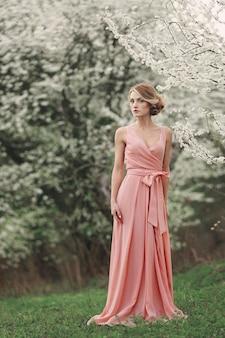 Vrouwendag. volledige lengte stijlvolle jongedame in de buurt van bloeiende boom in het voorjaar park. blond meisje met kapsel in roze jurk. bloeiende bomen
