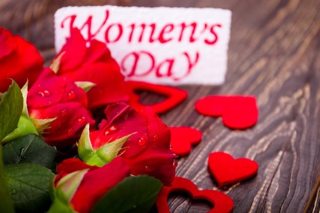 Vrouwendagkaart en bloemen. harten en natte rozen. druk uit door daden, niet door woorden. cadeau voor charmante dame.