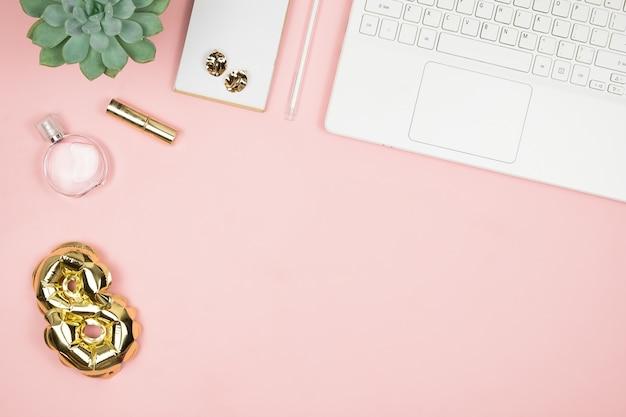 Vrouwendesktop met laptop, parfum, goudfolie-ballon 8 en copyspace. bovenaanzicht fijne vrouwendag. 8 maart gefeliciteerd.