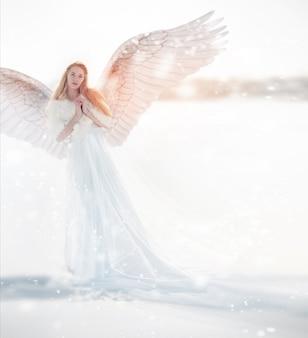 Vrouwenengel met vleugels in de winter. sneeuw