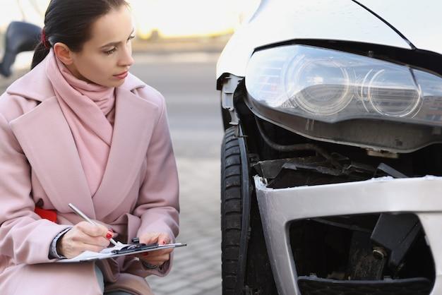 Vrouwenexpert die documenten invult in de buurt van kapotte auto op straat die de reparatiekosten schat