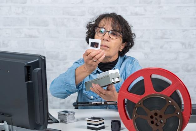 Vrouwenfotograaf die filmdia bekijken