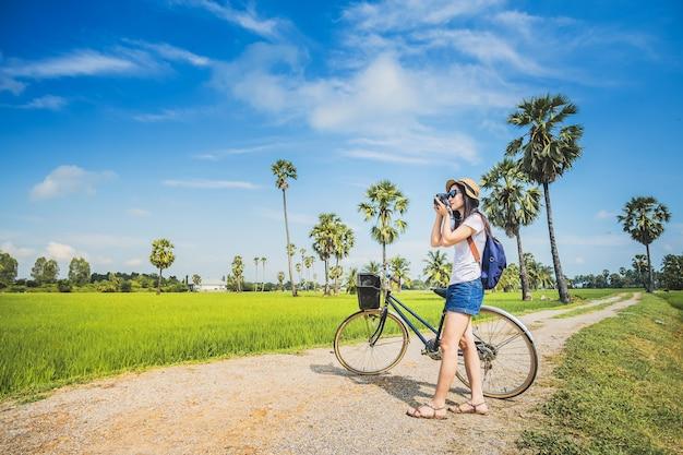 Vrouwenfotograaf die foto voor mening van padieveld nemen door camera.