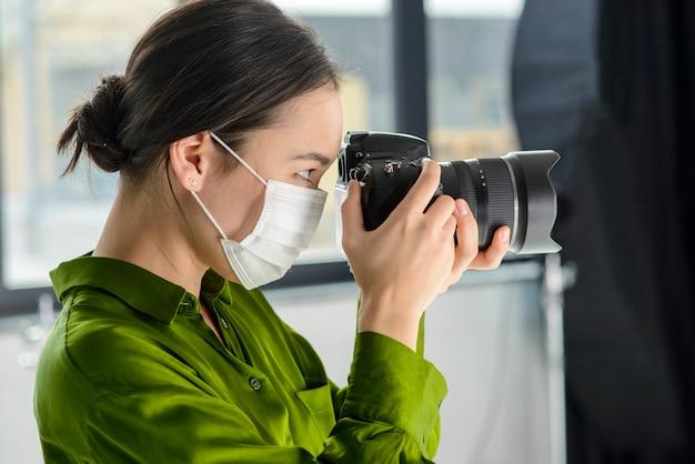 Vrouwenfotograaf die masker draagt