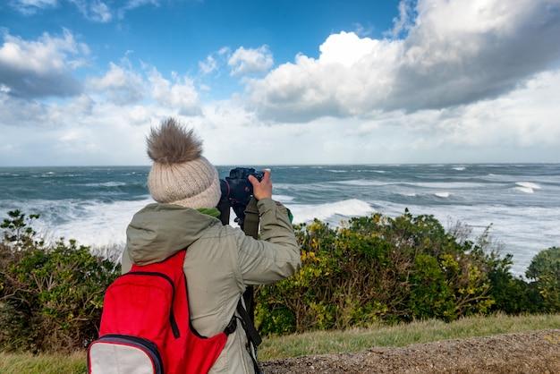 Vrouwenfotograaf die tijdens een storm in biarritz frankrijk werken
