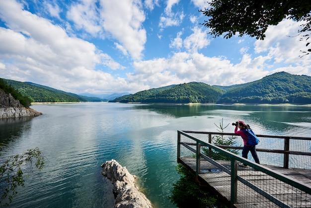 Vrouwenfotograaf met een blauwe rugzak op het meer