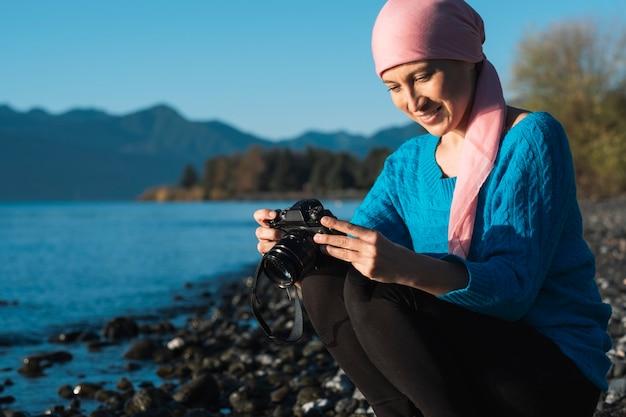 Vrouwenfotograaf met kanker maakt een foto van het landschap.