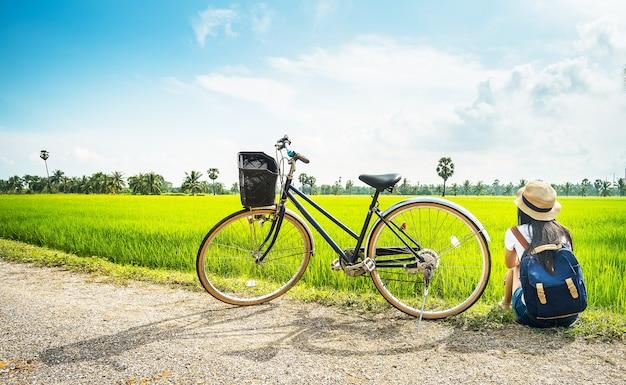 Vrouwenfotograaf zitting dichtbij fiets en nemend foto voor mening van padieveld door camera