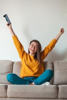 Vrouwengamer die online spel voor mobiele telefoons speelt, winnaar, in handen zittend op de bank