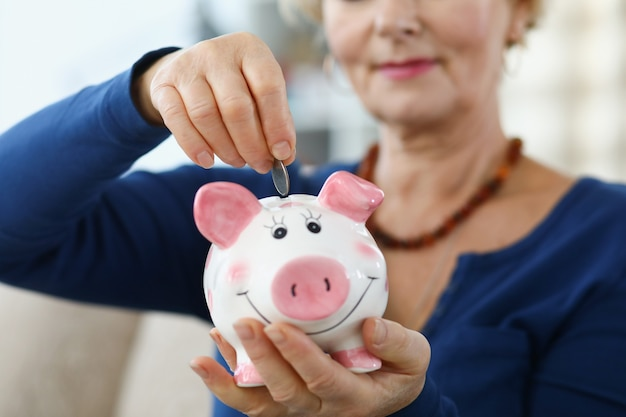 Vrouwengepensioneerde die muntstuk in roze spaarvarkenclose-up invoegen