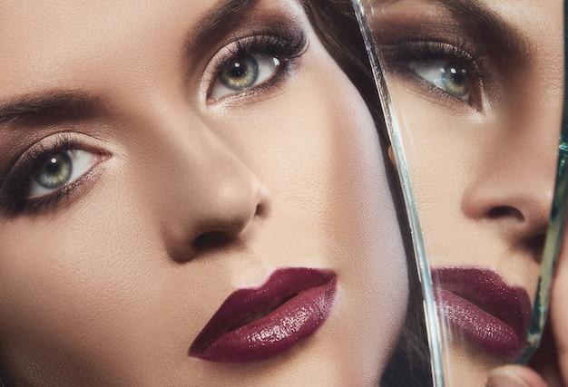 Vrouwengezicht en de scherf van spiegel