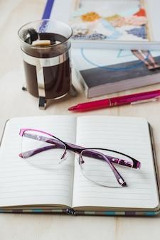 Vrouwenglazen met notitieboekje, koffie, potlood en boek