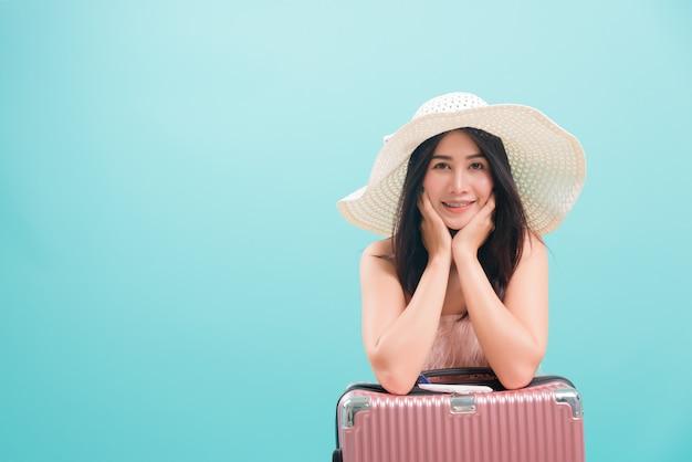 Vrouwenglimlach in de zomerreis om met hoed op kofferzak te reizen