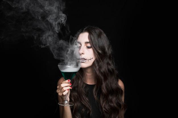 Vrouwengoblet die bij damp van rokende turkooise vloeistof ruiken