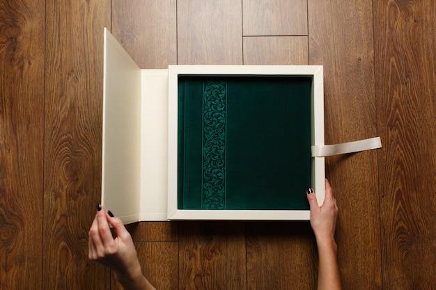 Vrouwengreep fotoboek met textielomslag in kartonnen doos. persoon open fotoalbum met heldere omslag
