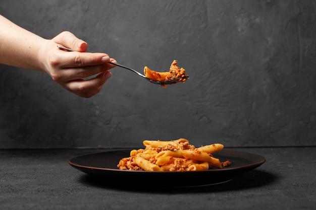 Vrouwengreep in deegwaren bolognese van vork de verse italiaanse penne op donkere plaat en donkere concrete achtergrond.