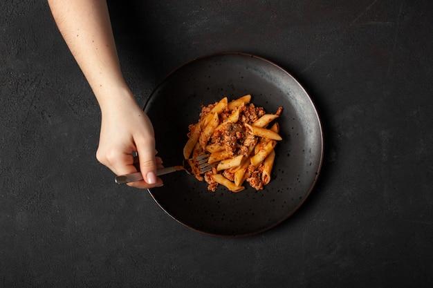 Vrouwengreep in deegwaren bolognese van vork verse italiaanse penne op donkere plaat en donkere concrete hoogste mening als achtergrond.
