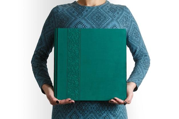 Vrouwengreep vierkant familie fotoboek met print met ruimte voor tekst. voorbeeld groen familie fotoalbum in handen van de vrouw met suède omslag. Premium Foto