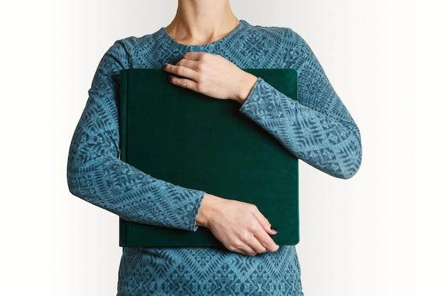Vrouwengreep vierkant familie fotoboek met print met ruimte voor tekst. voorbeeld groen familie fotoalbum in handen van de vrouw met suède omslag.