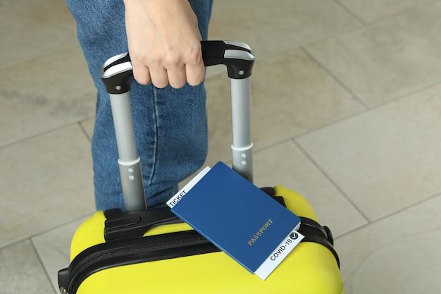 Vrouwengreepkoffer met paspoort met kaartje en covid - 19 mark