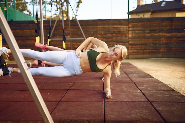 Vrouwengroep abs oefening met touwen op sportveld, vooraanzicht, buiten fitnesstraining