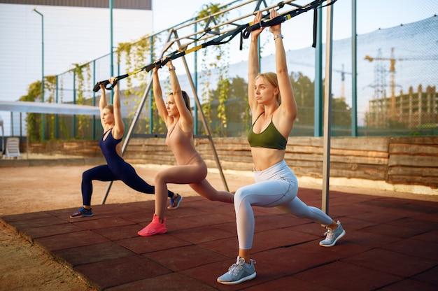 Vrouwengroep doet fitness oefening met touwen op sportveld, buiten training