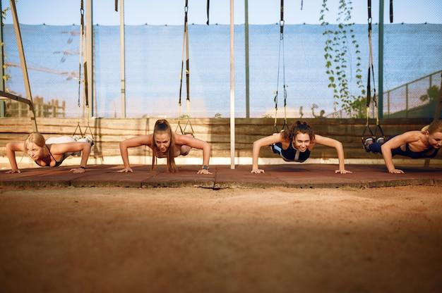 Vrouwengroep doet push-ups op sportveld, vooraanzicht, buiten fitnesstraining