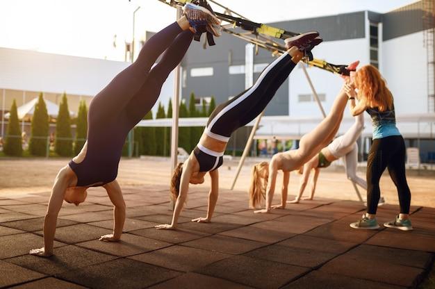 Vrouwengroep met instructeur op sportveld, vooraanzicht, buiten fitnesstraining