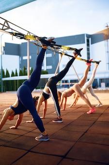 Vrouwengroep op sportveld, vooraanzicht, buiten fitnesstraining