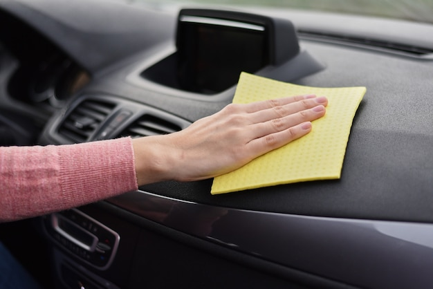 Vrouwenhand cleanin autodashboard met gele microfiberhanddoek. schoonmaak auto concept