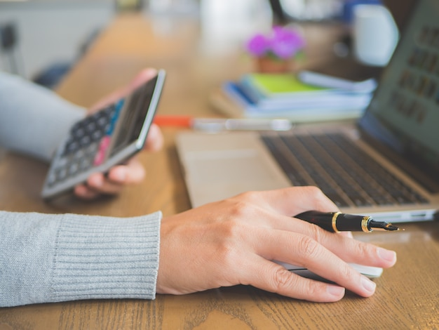 Vrouwenhand die aan haar laptop met calculator werken. sociaal netwerktechnologie concept.