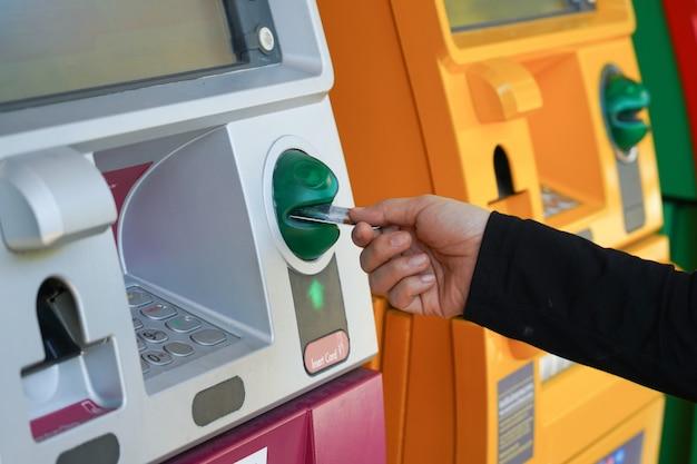 Vrouwenhand die creditcard gebruiken om geld van geldautomaat op te nemen of over te maken.