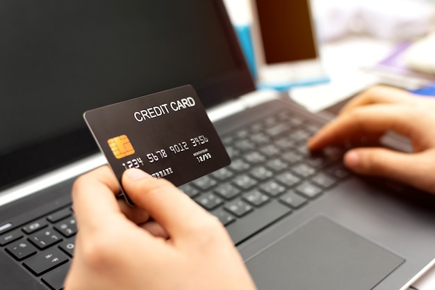 Vrouwenhand die creditcard houdt en laptop computer met behulp van. online winkelconcept.