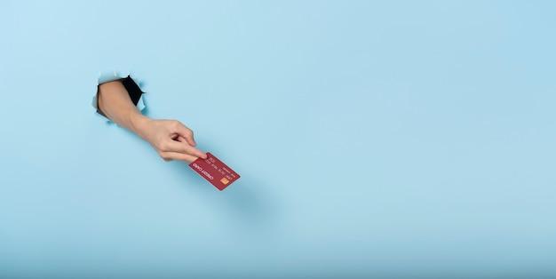 Vrouwenhand die creditcard op blauwe bannerachtergrond houden. panoramisch beeld