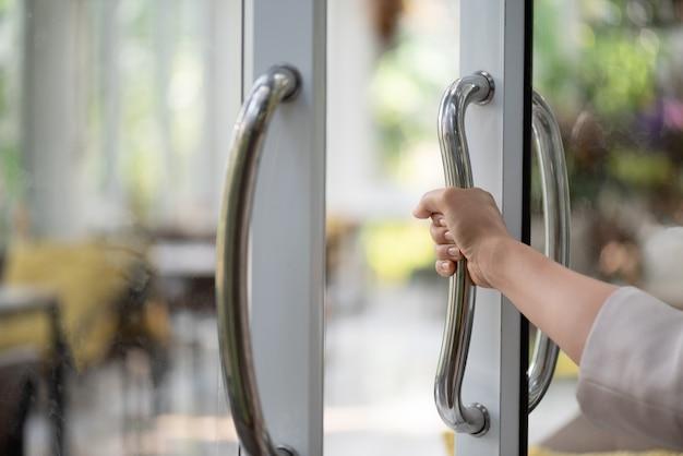 Vrouwenhand die de deurbar houden om de deur te openen