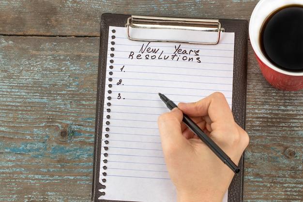 Vrouwenhand die de resoluties van het nieuwe jaar schrijven. new year's resolutie concept.