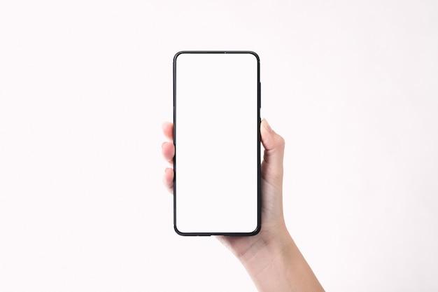 Vrouwenhand die de zwarte smartphone met het lege scherm houden dat op witte achtergrond wordt geïsoleerd