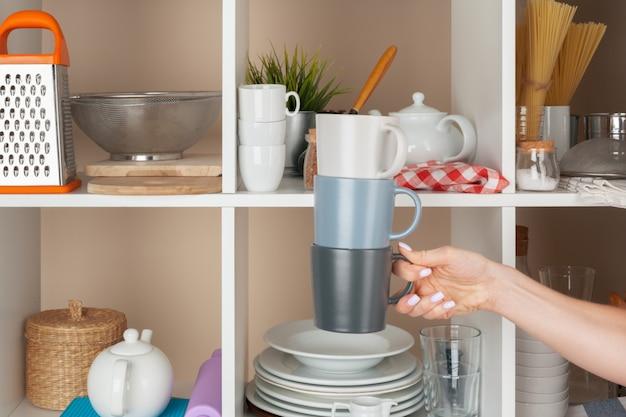 Vrouwenhand die dishwarestukken van plank in keuken nemen