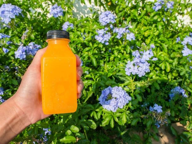 Vrouwenhand die een fles jus d'orange klaar houden te drinken. in de bloementuin